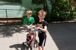Sammy and Jayson ride their bikes and scooters.