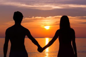 Romantic Valentine's Day scene of a young couple silhouettes holding hands by the sea staring at colorful sunset in the island of Koh Phangan, Thailand. Love scene concept