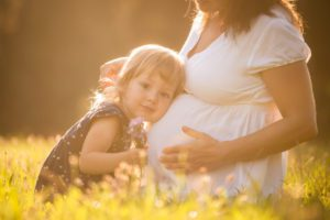 Little child listening baby in belly of her mother outdoor in sunny nature